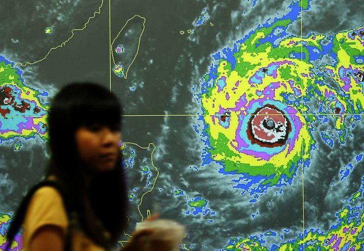 Una taiwanesa pasa por delante de una pantalla con un gráfico del tifón Nepartak que se aproxima hacia Taiwán, dentro de la Agencia Meteorológica en Taipei, Taiwán. (EFE)
