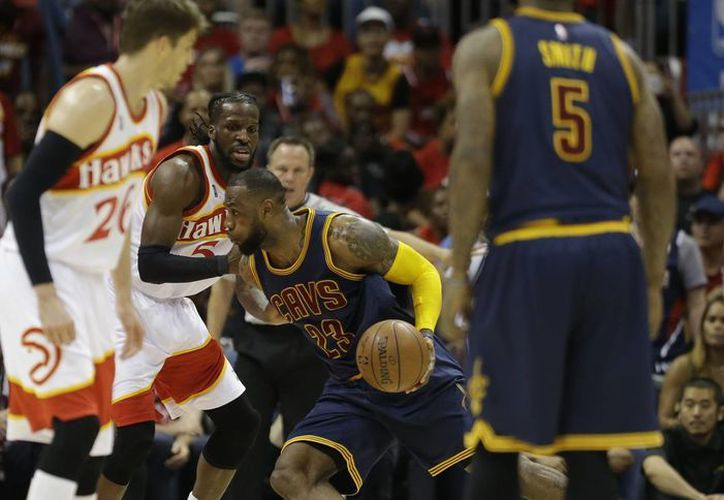 LeBron James (23), de Cavaliers, esquiva a DeMarre Carroll (5), de Hawks de Atlanta, en el segundo partido consecutivo de playoffs ganado por Cleveland. (Foto: AP)