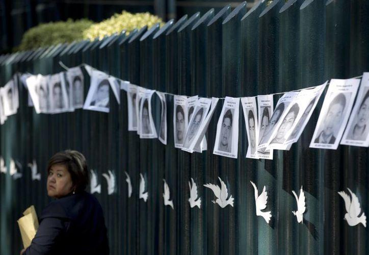 Una mujer pasa frente a la sede de la PGR, en la ciudad de México, donde se colocaron fotos de los estudiantes de Ayotzinapa desaparecidos, el 29 de octubre de 2014. (Foto:AP)