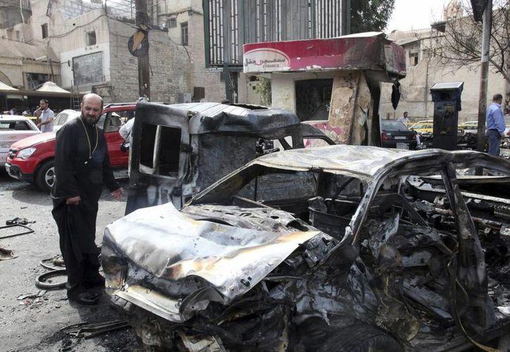 Reportan que una bomba estalló en un mercado al aire libre en Mahmudiyah, son el saldo de ocho muertos. Imagen de contexto donde miembros de los equipos de rescate inspeccionan el lugar donde estalló un coche bomba en Irak. (EFE/Archivo)