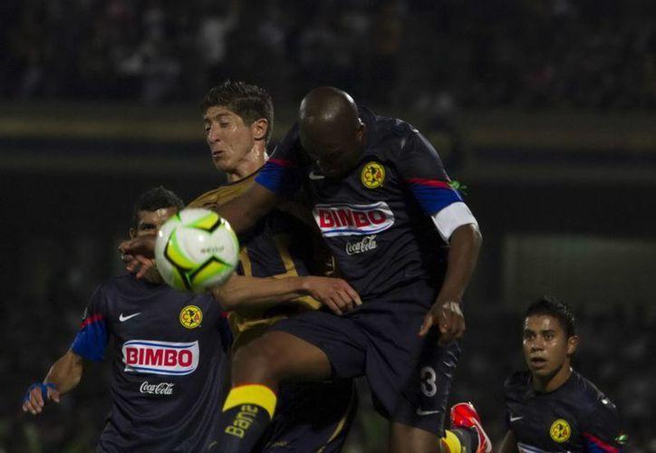 El defensor americanista Aquivaldo Mosquera (3) disputa el esférico con el defensa Palacios. (Notimex)