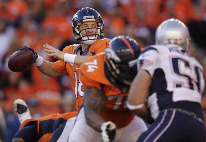 El quarterback Peyton Manning de los Broncos de Denver lanza un pase contra los Patriots de Nueva Inglaterra. (Agencias)