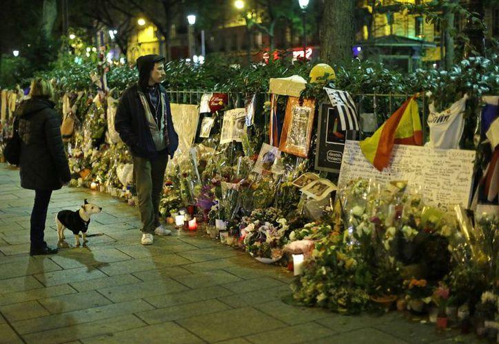Unas personas observan los ramos de flores dejados para las víctimas de los atentados, afuera del centro de conciertos Bataclan, en París. (Agencias)