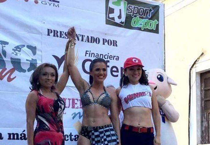 Paola Gabriela Betancourt (c), ganadora del 'Guerreras del Mayab', evento que se realizó dentro del 'Strong Man Yucatán 2016'. (Milenio Novedades)