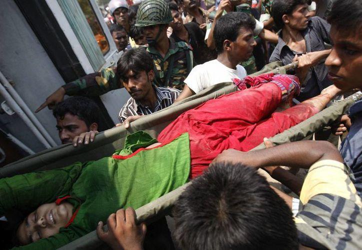Un grupo de personas rescata a una trabajadora herida tras el derrumbe de un edificio de ocho plantas en Dacca, Bangladesh. (EFE)