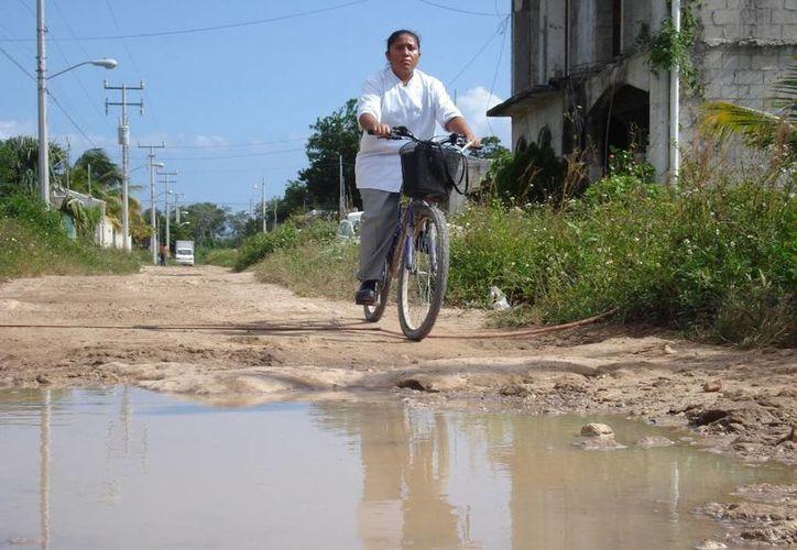 Los ciclistas de Tulum lidian a diario con baches, basura y además con automovilistas con poca precaución.  (Rossy López/SIPSE)