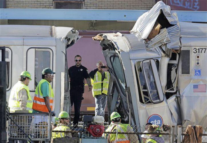 Autoridades inspeccionan un vagón dañado en el choque entre los dos trenes. (Agencias)