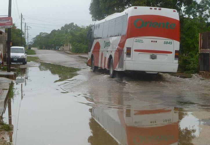En las salidas de la cabecera municipal se registran encharcamientos. (Raúl Balam/SIPSE)