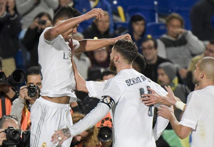 El brasileño Casemiro (izq) celebra con sus compañeros el gol que les dio la victoria al minuto 89, con la que continúan como terceros de la Liga BBVA de España. (Imágenes de AP)