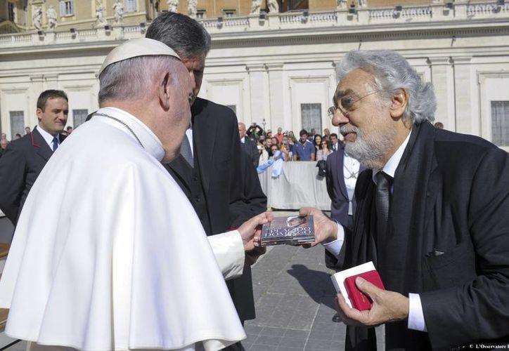 El Papa Francisco y Plácido Domingo se reunieron al finalizar la audiencia general en Plaza San Pedro. El tenor aprovechó el momento para regalar uno de sus disco al Pontífice.(AP)
