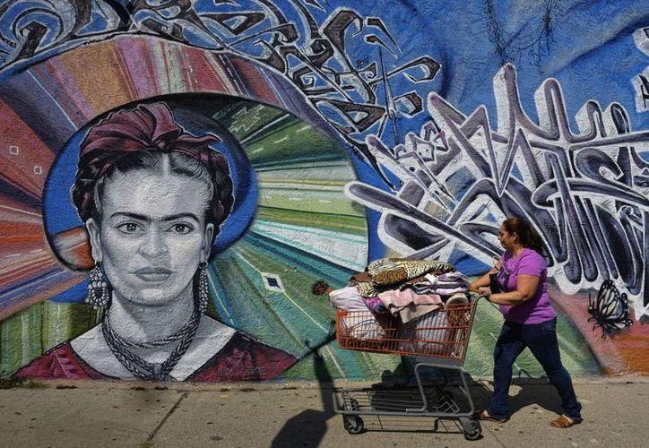 Una mujer pasa frente a un mural callejero alusivo a Frida Kahlo pintado por el artista callejero Levi Ponce en el barrio Pacoima de Los Ángeles, California, EU. (Agencias)