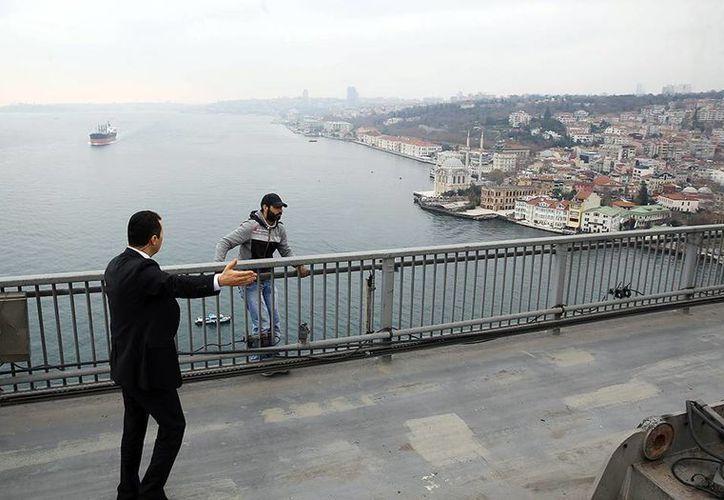 Vezir Çatras, de 30 años, intentaba tirarse de un puente de 65 metros de altura debido a que terminó con su esposa. Después de platicar con el presidente desistió a la idea. (Imágenes de AP)