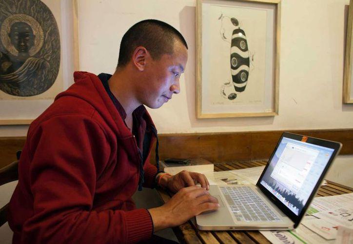 El monje budistaJamyang Palden utiliza su laptop para acceder a sus mensajes en un café con WiFi en Dharmsala, India. (Agencias)