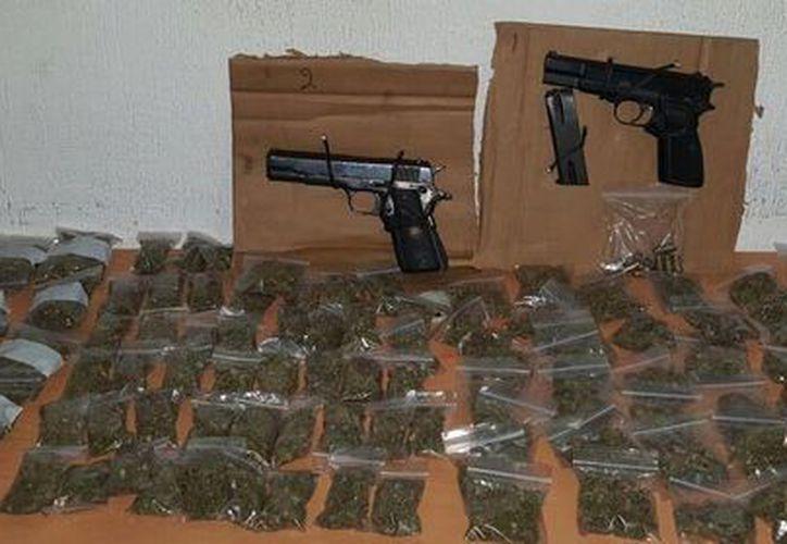 Les fueron aseguradas dos armas y 130 bolsitas de plástico con marihuana. (Redacción/SIPSE)