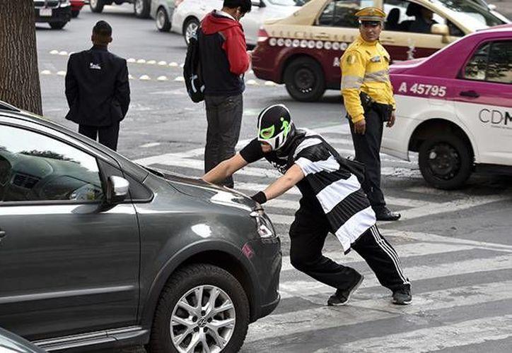 Entre las 'misiones' de Peatonito está el empujar a los coches que bloquean la calle a los peatones o invaden los pasos de cebra. El objetivo centraL es evitar muertes de peatones. (Afp)