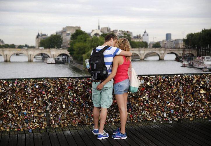 Una pareja se besa en el Pont des Arts, en París, Francia, de donde serán retirados los 'candados del amor'. EFE/Archivo