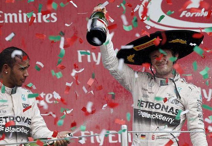 Nico Rosberg y Lewis Hamilton festejan en el podio del Gran Premio de México, este domingo. Con esta victoria Rosberg rebasa a Sebastian Vettel en el  Campeonato de Pilotos y quedó en la segunda posición. (AP)