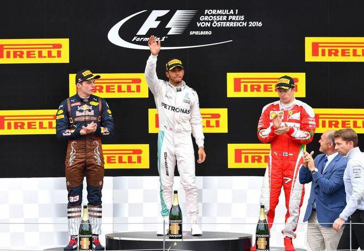 El piloto Max Verstappen, (izq), el ganador Lewis Hamilton (centro) y Kimi Raikkonen (der) de Finlandia, en la premiación de la Fórmula Uno Gran Premio, en el circuito Red Bull Ring de Spielberg, el sur de Austria. (Foto AP / Kerstin Joensson)