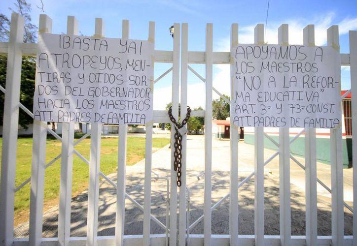 Los jefes de familia también colocaron carteles en las rejas de las escuelas. (Harold Alcocer/SIPSE)