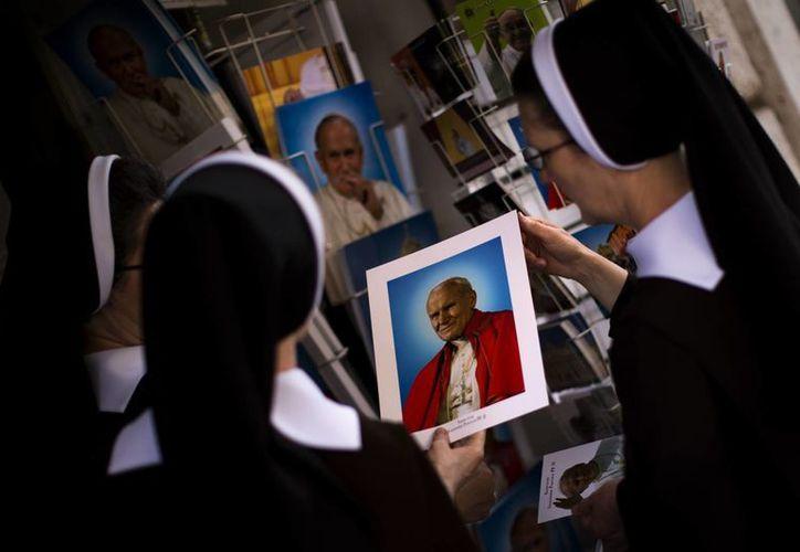 Monjas compran retratos del Papa Juan Pablo II, en una tienda cerca de la plaza de San Pedro en el Vaticano. (Agencias)