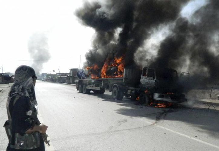 Un oficial de seguridad paquistaní observa cómo se consume un camión que transportaba vehículos de la OTAN tras ser objetivo de un ataque cerca de la frontera con Afganistán, en Jamrud, Pakistán, el pasado lunes. (EFE)