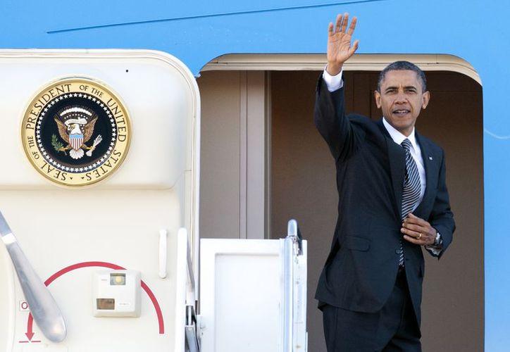 El presidente Obama se despide antes de ingresar al avión Air Force One en la Base Andrews de la Fuerza Aérea de EU. (Agencias)