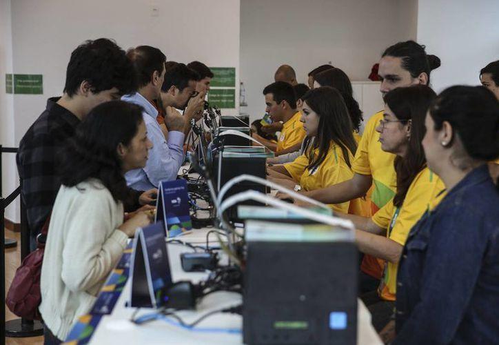 Brasileños acuden a un centro comercial a comprar los boletos para ingresar a los Juegos Olímpicos y Paralímpicos Río 2016 en Río de Janeiro, Brasil, este 20 de junio de 2016. (EFE)