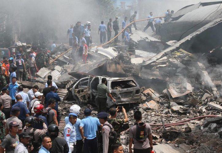 Bomberos y personal militar inspeccionan el lugar donde se estrelló un avión de transporte del ejército indonesio, en Medan, en el norte de la isla de Sumatra, Indonesia, este martes. (Foto AP/Gilbert Manullang)
