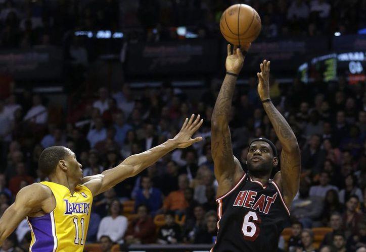 Pese a la marca de Wesley Johnson, LeBron James logra hacer un enceste de tres puntos en duelo Heat vs Lakers. (Agencias)