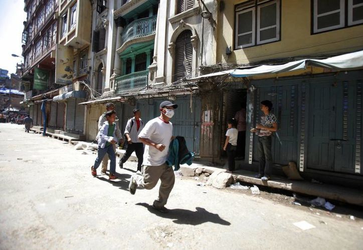 Un hombre nepalí corre para ponerse a salvo tras el segundo gran terremoto que sacude Katmandú, la capital de Nepal, en menos de tres semanas, este martes. (Foto AP/Bikram Rai)