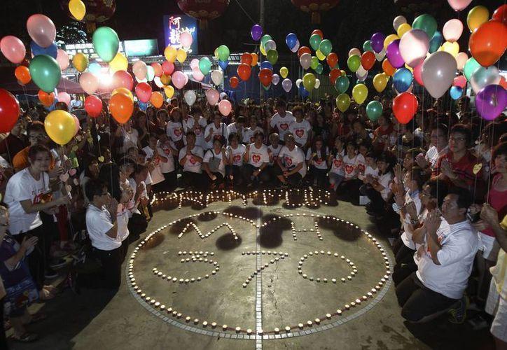 """Una multitud en Kuala Lumpur sostiene globos junto a un mensaje en el que se lee """"ora por el vuelo MH370"""". (Agencias)"""