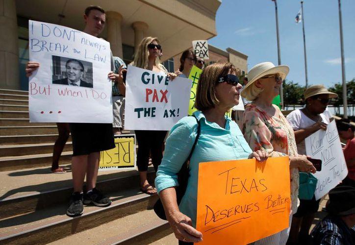 Un grupo de personas se manifestó a las puertas del Palacio de Justicia en Plano, Texas, para solicitar la dimisión de Ken Paxton como procurador de Justicia de Texas, tras ser fichado por tres delitos. (AP Foto/Tony Gutierrez)