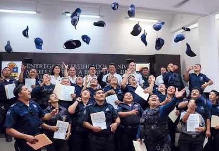 reviviendo la peculiar forma de celebrar de los graduados, los agentes culminaron la ceremonia de entrega de certificados. (Redacción/SIPSE)