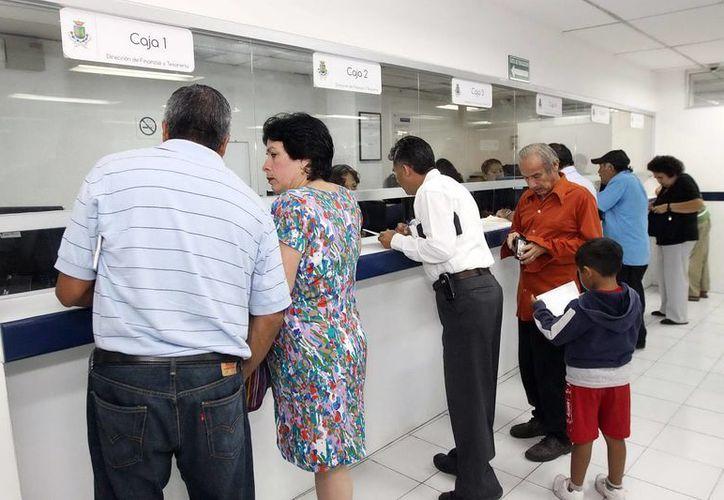 El Ayuntamiento espera captar 487 millones de pesos en impuestos. En la imagen, ciudadanos realizan pagos en una oficina recaudadora de Mérida. (Milenio Novedades)