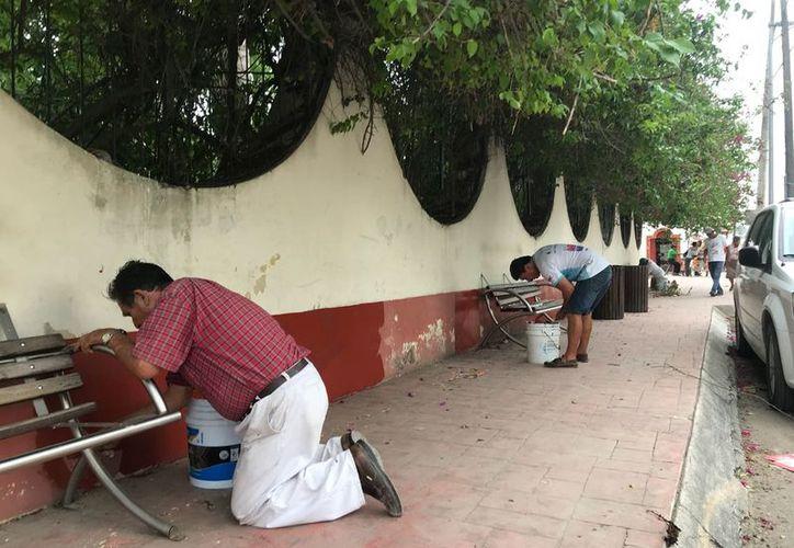 Un grupo de ciudadanos pintan la barda de la parroquia. (Javier Ortiz/SIPSE)