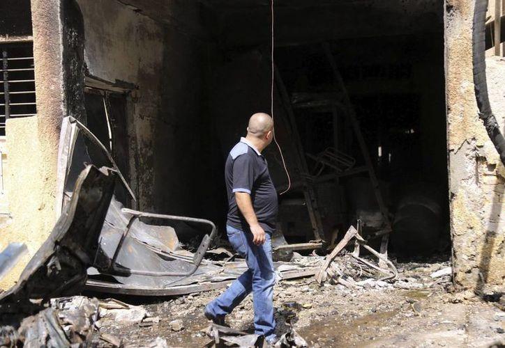Un hombre iraquí camina en la zona donde se registró un atentado con coche bomba en Bagdad. (EFE)