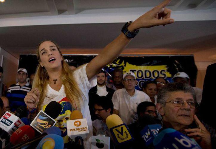 La esposa del opositor venezolano Leopoldo López, Lilian Tintori (c), ofrece declaraciones a periodistas este jueves en la ciudad de Caracas (Venezuela) tras denunciar un atentado en su contra. (AP)