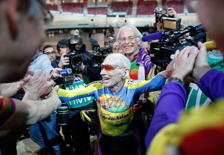 El centenario ciclista recibió una cerrada ovación y fue rodeado por fotógrafos y camarógrafos al llegar a la meta en el nuevo Velódromo Nacional de Francia, tras romper su marca. (Agencias)