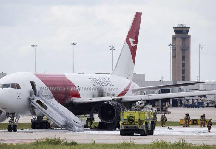 Un grupo de bomberos a un lado del Boeing 767 incendiado el día de hoy en el Aeropuerto Internacional de Fort Lauderdale-Hollywood en Florida. El avión se dirigía a Caracas, Venezuela. (Foto AP/Wilfredo Lee)