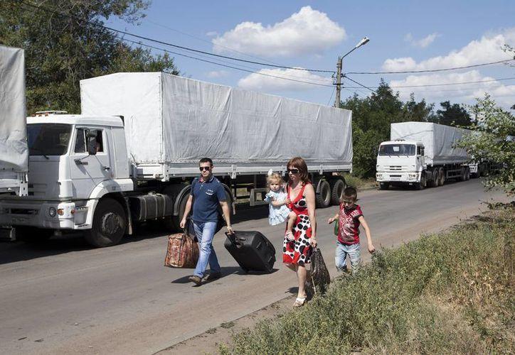 Una familia pasa frente a una columna de camiones de ayuda rusos estacionados en un camino cerca de un puesto de control fronterizo con Ucrania. (Agencias)