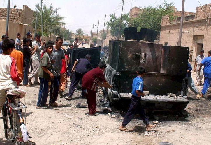 Aviones iraquíes bombardearon el convoy del líder máximo del Estado Islámico, pero se desconoce si él murió. En la foto, jóvenes iraquíes rodean un convoy militar que fue objetivo de la explosión de una bomba en una carretera en Samarra, Irak. (EFE/Archivo)