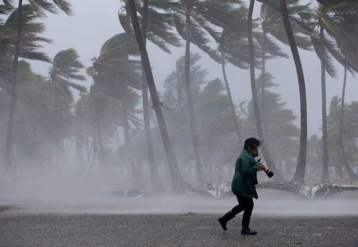 Los vientos sostenidos máximos de 'Joaquín' rondaban los 120 kilómetros por hora. Una mujer es vista durante una fuerte tormenta en el Caribe. (Archivo/EFE)