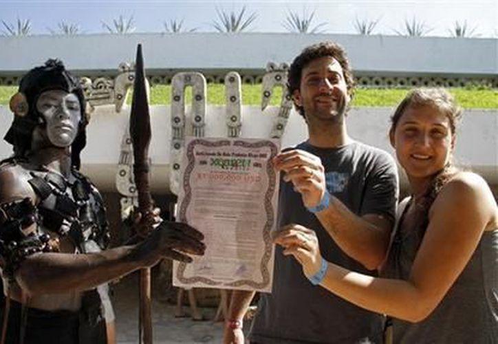 Un hombre con atuendo indígena le entrega a dos turistas un certificado del hotel Xcaret de Playa del Carmen. (Agencias)