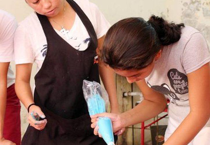 Dentro de la clausura de los talleres 'Alas y Raíces de Yucatán' se realizaron exposiciones de manualidades, función de títeres y elaboración de pasteles. En la foto, las participantes del taller elaboran un pastel.(Milenio Novedades)