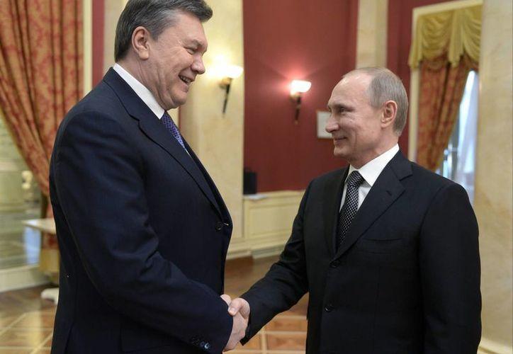 Vladimir Putin (d), mandatario de Rusia, se saluda con el depuesto presidente de Ucrania, Viktor Yanukovich. La foto corresponde al 7 de febrero, previo al inicio de los Juegos Olímpicos en Sochi, Rusia. (Agencias)