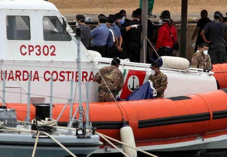 Varios militares permanecen junto a una embarcación que naufragó el 7 de octubre. (Archivo/EFE)