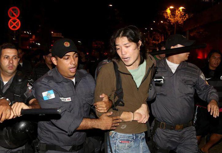 Manifestantes detenidos por policías antidisturbios este martes 17 de junio de 2014, en Río de Janeiro, Brasil. (EFE)