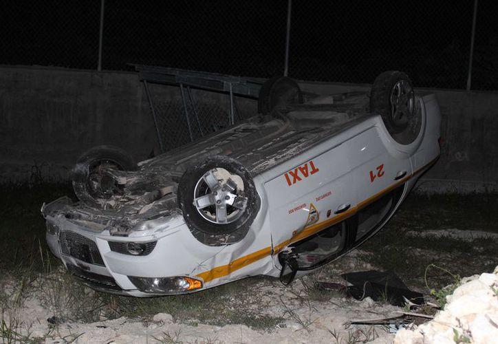 Los hombres, al tratar de huir, se impactaron en un montículo de tierra y acabaron por volcar el taxi. (Redacción/SIPSE)