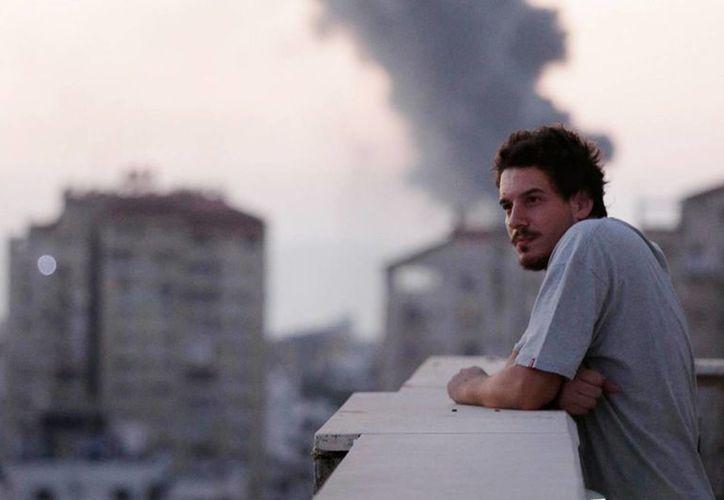 Imagen de agosto de 2014 que muestra al fallecido periodista de AP, Simone Camilli, en el balcón de su habitación, desde donde se aprecia una columna de humo a causa de los ataques de Israel en la Franja de Gaza. (Foto: AP/Lefteris Pitarakis)