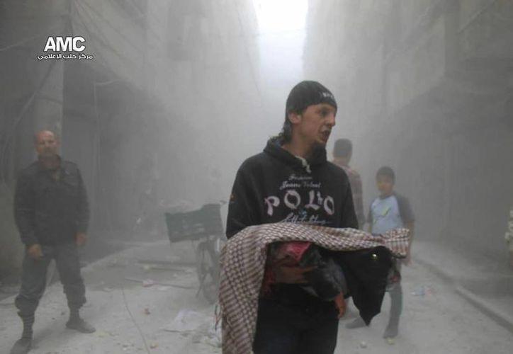 Un hombre carga el cadáver de un niño que murió durante un ataque de las fuerzas del gobierno contra el vecindario de Al-Ansari, en Alepo, Siria. (Agencias)